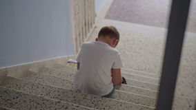 Offended child sitting on the stairs stock video