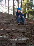 Boy sitting on stairs and looking into the distance Royalty Free Stock Photos