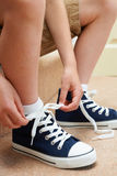 Boy Sitting On Stairs Tying Shoelaces Stock Photo