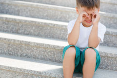 The boy sitting on the stairs in the underpass Royalty Free Stock Photos