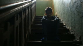 The boy is sitting on the steps of an abandoned porch. The concept of children`s drug addiction, vagrancy, homelessness. stock video footage