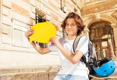 Boy sitting on the steps with empty speech bubble. Teenage boy sitting on the steps outdoors with yellow blanked speech bubble Royalty Free Stock Image