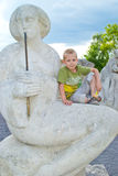 Boy sitting on a stone statue. Boy sitting on a stone female figure Stock Photo