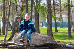 The boy sitting on the stone Stock Images
