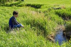 Boy Sitting by Stream Stock Photos