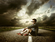 Boy sitting in street Stock Image