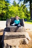 Boy Sitting on Stump Chair Royalty Free Stock Photos