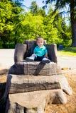 Boy Sitting on Stump Chair Royalty Free Stock Photos