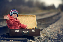 Boy sitting in a suitcase near railway journey Royalty Free Stock Image