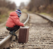 Boy sitting with  suitcase near the railway journey Stock Photography