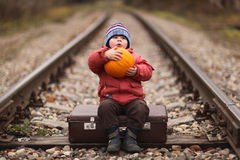 Boy sitting on  suitcase near the railway journey Stock Photography