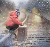Boy sitting with  suitcase near the railway journey Royalty Free Stock Photography