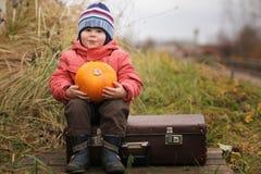 Boy sitting on suitcase Stock Photo