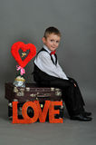 Boy sitting on a suitcase with the words love. Boy in the suitcase with the words love and hearts Royalty Free Stock Photo