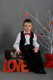 Boy sitting on a suitcase with the words love. And white tree with red hearts Stock Photos