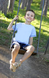 Boy sitting on a swing Stock Photo
