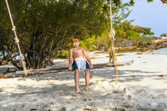 Boy sitting on a swing at the beach Stock Image