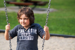 Boy sitting on a swing Royalty Free Stock Image