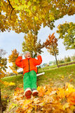 Boy sitting on swings, smiling during autumn day Stock Photos