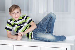 Boy sitting on a table with digital tablet Royalty Free Stock Images