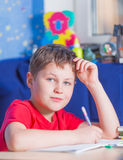 Boy sitting at the table and doing his homework Royalty Free Stock Photo