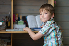 Boy sitting at table doing homework. Looking at the camera Royalty Free Stock Photography