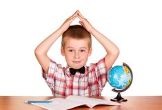 Boy sitting at the table, holding up their hands, near globe and notepad isolated on white. Background Stock Photography