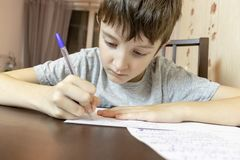 A boy sitting by the table at home and writing with a pen on paper royalty free stock image