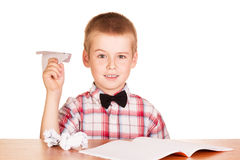 Boy sitting at  table and make paper planes isolated. Cute little boy sitting at a table and make paper planes isolated on white background Royalty Free Stock Image