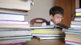 Boy sitting at a table with a stack of books. child reading. boy with glasses