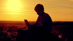 Boy sitting with a tablet gadget at sunset stock video footage