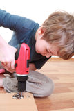 Boy sitting and tightening screws in board Royalty Free Stock Photography