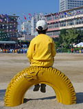 Boy sitting on tire Stock Images