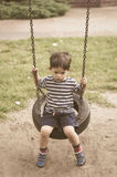 Boy sitting on tire swing set. Young boy sitting on a tire swing set on a playground on August 2017 in Poznan, Poland in sepia film look Stock Images