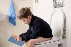 Boy sitting on the toilet and reading a book. Little 6 year old boy sitting on the toilet and reading a blue book royalty free stock photography