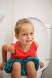 Boy sitting on the toilet Royalty Free Stock Image