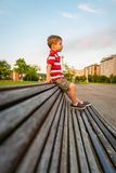 Boy sitting on the top of bench park relaxing Royalty Free Stock Photo