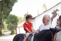 A boy sitting on top of a black horse listening to his grandfather's instruction. A little boy sitting on top of a black horse listening to his grandfather's royalty free stock photo