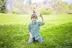 Boy sitting tossing up fresh picked flowers. Smiling Happy five year old boy sitting on the grass outside with a bouquet of picked yellow dandelions playfully royalty free stock photos