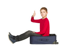 Boy sitting on travel bag holding showing thumb up Stock Photo