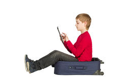 Boy sitting in travel bag using tablet isolated on white Stock Photo
