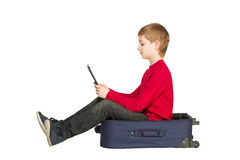 Boy sitting in travel bag using tablet pc isolated on white Stock Photos