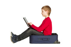 Boy sitting in travel bag using tablet pc isolated on white Royalty Free Stock Photo