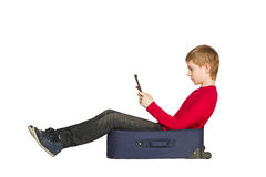 Boy sitting in travel bag using tablet pc on white Stock Image