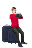Boy sitting on travel bags holding empty wallet isolated on whit Royalty Free Stock Photos
