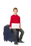 Boy sitting on travel bags holding sheet of paper isolated on wh Stock Image