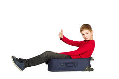 Boy sitting on travel bags holding showing thumb up Stock Image