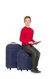 Boy sitting on travel bags holding tablet isolated on white Royalty Free Stock Photos