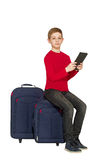 Boy sitting on travel bags holding tablet pc isolated on white Royalty Free Stock Images