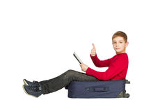 Boy sitting on travel bags holding tablet shoeing thumb up Stock Image